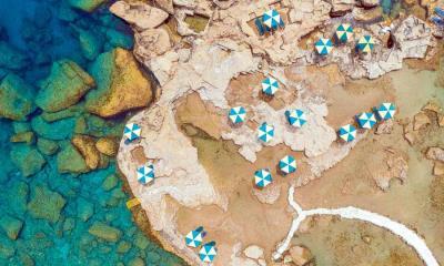 2020.06.24 - 鸟瞰希腊罗德岛岩石海岸上蓝白相间的遮阳伞