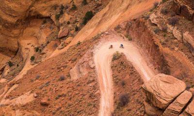 两名山地车骑手在白缘公路上沿着谢福小道的转弯处骑行 ,犹他州峡谷地国家公园
